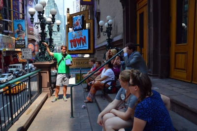 Broadway Up Close Tour Guide Drew Pournelle with the tour on the stairs of the New Victory Theatre